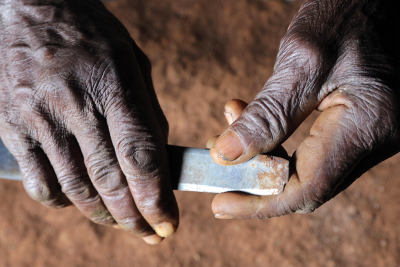 Knife used for girls' genital cutting in the hands of an old circumciser woman.