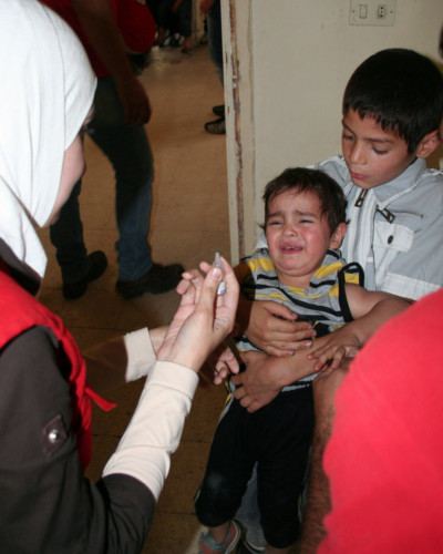 A volunteer of the Syrian Arab Red Crescent administers oral polio vaccine to a crying child as part of a campaign to extinguish an outbreak of the disease in 2014.